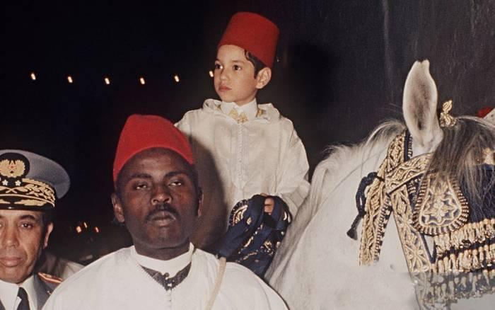 Le prince héritier Sidi Mohammed sur un cheval, se dirigeant vers le Mausolée Moulay Driss à Fès au mois de mars 1971 à l'occasion de sa circoncision, conformément aux traditions ancestrales des Alaouites © DR