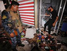 Des Irakiens inspectent les dégâts dans un marché de Bagdad après un attentat meurtrier, le 19 juillet 2021 © AFP