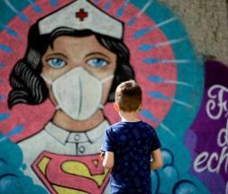 Un garçon se tient devant un graffiti peint par l'artiste Kai 'Uzey' Wohlgemuth à Hamm, en Allemagne de l'Ouest, le 8 avril 2020. ©️ AFP via Getty Images
