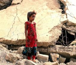 Une fillette yéménite, déplacée avec sa famille, se tient au milieu des ruines d'un immeuble détruit par des frappes aériennes de la coalition menée par l'Arabie saoudite, dans la province de Hajjah au nord-ouest du Yémen, le 3 août 2019 © AFP