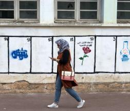 Une Marocaine passe devant des emplacements où sont peints les symboles des partis politiques du Royaume, le 4 septembre 2015 © AFP/Archives