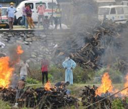 Des gens assistent à la crémation de malades atteints de la Covid-19 décédés à Siliguri au Bengale occidental en Inde le 4 mai 2021 © AFP