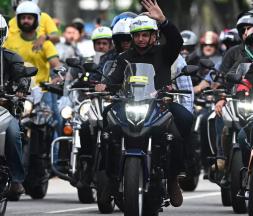Le président brésilien Jair Bolsonaro salue ses partisans lors d'une parade à moto, le 23 mai 2021 © AFP