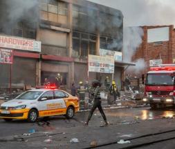 Une femme marche près d'un camion de pompiers en intervention après une nouvelle nuit de violences, à Johannesburg, en Afrique du Sud, le 12 juillet 2021. © Yeshiel Panchia, AP Photo