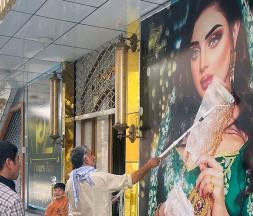 Une employée d'un salon de beauté peint une grande photo d'une femme sur un mur à Kaboul. Photo : Kyodo/AP