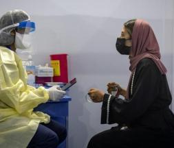 Une infirmière scanne un code avant d'administrer un vaccin contre la Covid-19 à une femme le 9 août 2021 à Errahma, près de Casablanca © AFP
