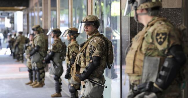 Des soldats non armés de la Garde nationale de Washington montent la garde devant un grand magasin, le lundi 1er juin 2020 à Seattle © Elaine Thompson/AP
