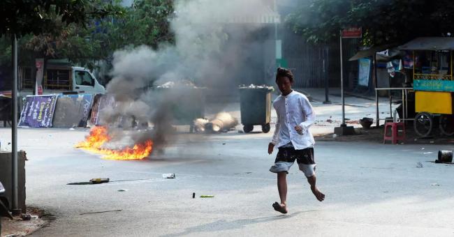 Un homme traverse la rue près d'une barricade en feu à Mandalay, en Birmanie, le 14 mars 2021 © AP