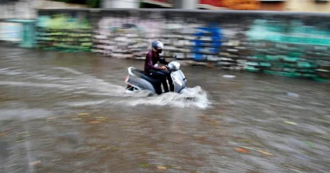 Un homme à scooter se fraie un passage dans une rue inondée à l'approche du cyclone Tauktae, à Bombay, en Inde, le 17 mai 2021 © AFP