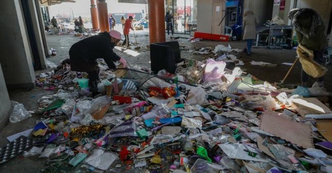 Des habitants utilisent des balais pour nettoyer le Diepkloof Square le 14 juillet © AFP