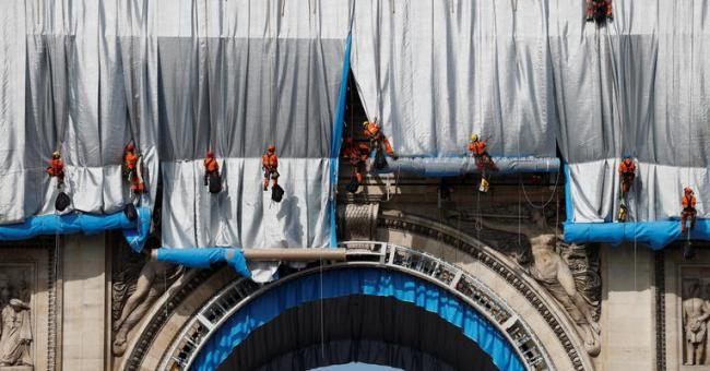 Des cordistes commencent à emballer l'Arc de Triomphe le 12 septembre 2021 © Reuters