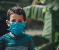 Un petit enfant portant un masque © DR
