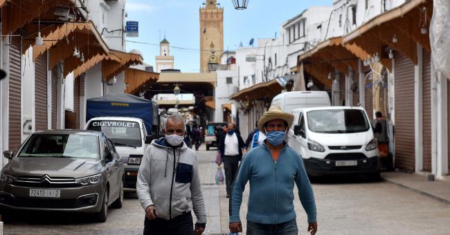 Hommes portant le masque, dans une rue d'une ville marocaine © DR