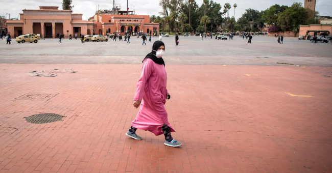 Une femme marocaine portant un masque de protection traverse la place Jemaa el-Fna, presque déserte, dans le centre de Marrakech, le 17 mars 2020. © Fadel Senna, AFP