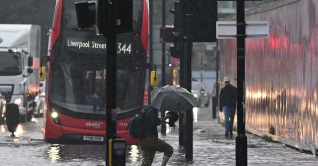 Un passant traverse une rue inondée de Londres après des pluies torrentielles © AFP/Justin Tallis
